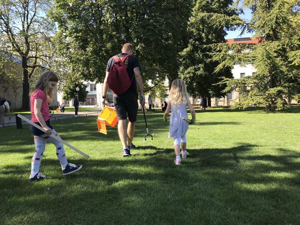 Papa sammelt Müll mit zwei Kindern
